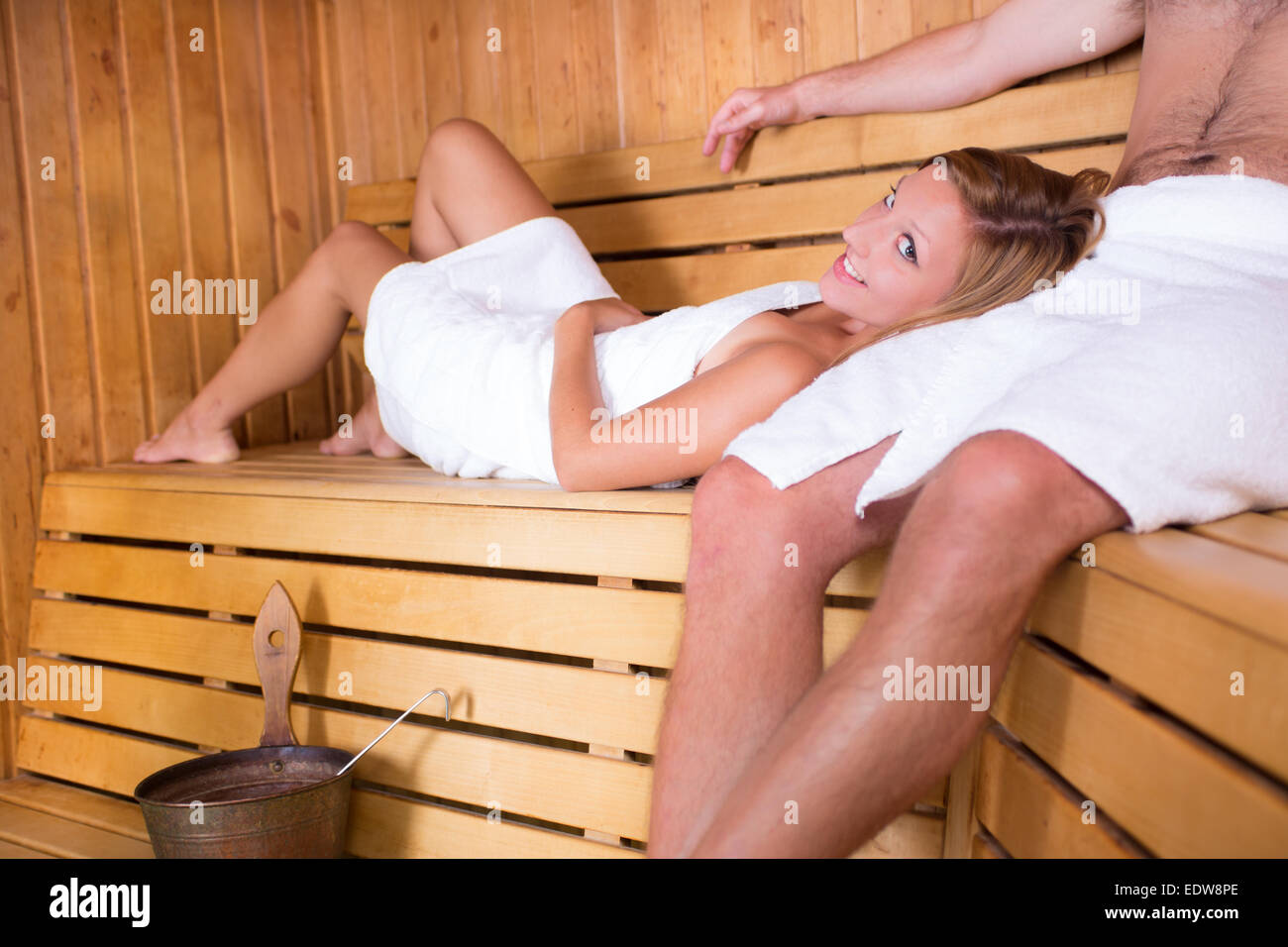 Couple relaxing in traditional wooden sauna. - Stock Image