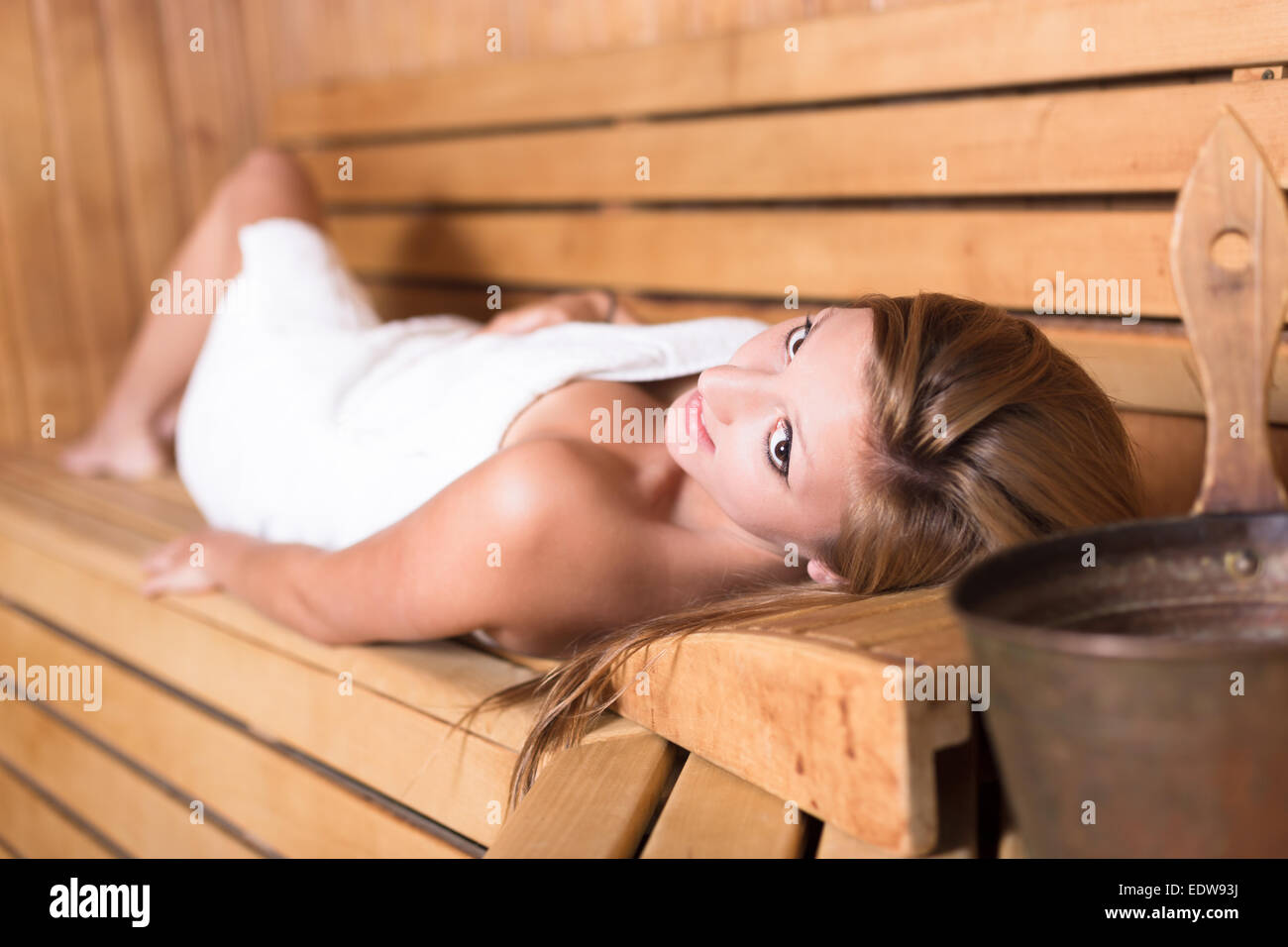 Lady relaxing in traditional wooden sauna. - Stock Image