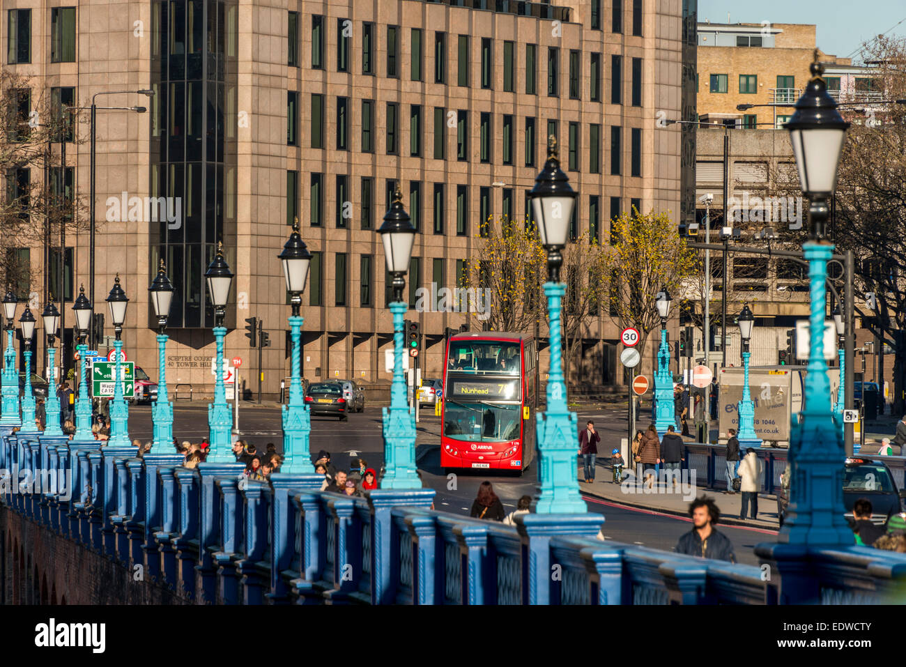 A London red bus entering Tower Bridge Approach, lined by streetlamps - Stock Image