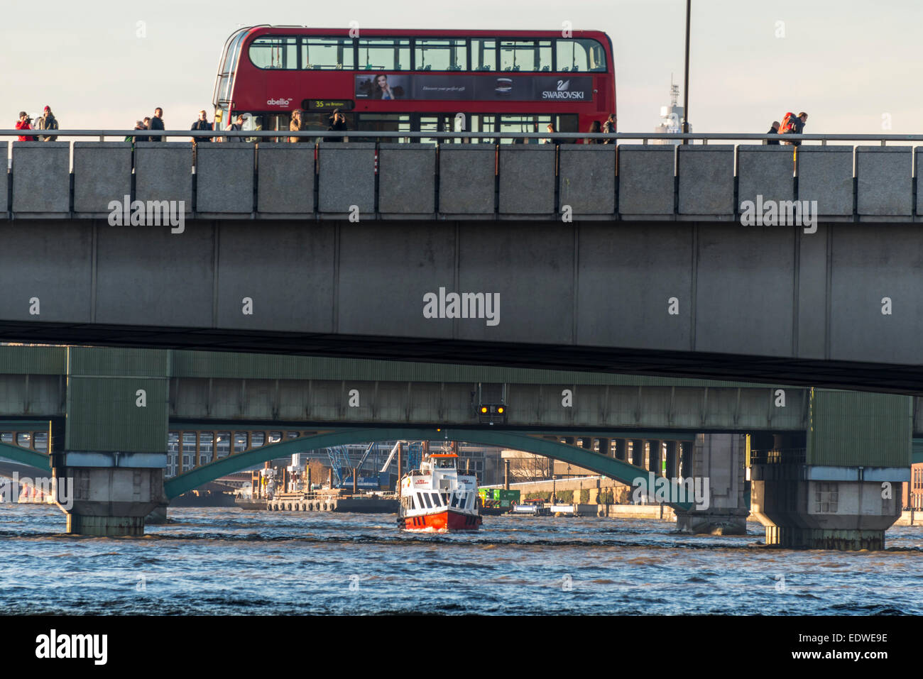 A London red bus passes over London Bridge while a River Thames cruise boat passes below Southwark Bridge. - Stock Image