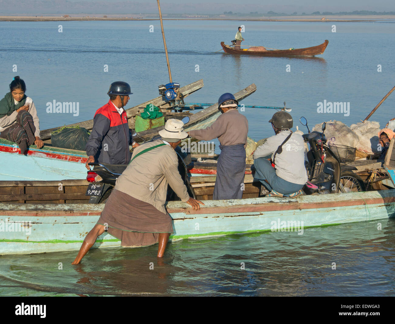 Boatmen by the Irrawaddy river loading and unloading goods and passengers, Myanmar - Stock Image