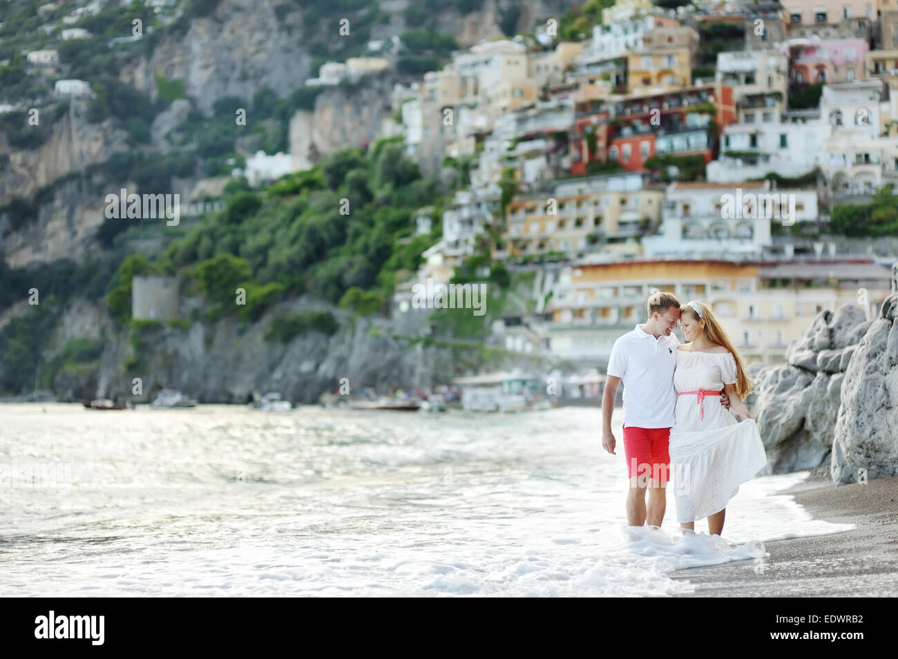 smiling happy young couple walking on the beach of Positano - Stock Image