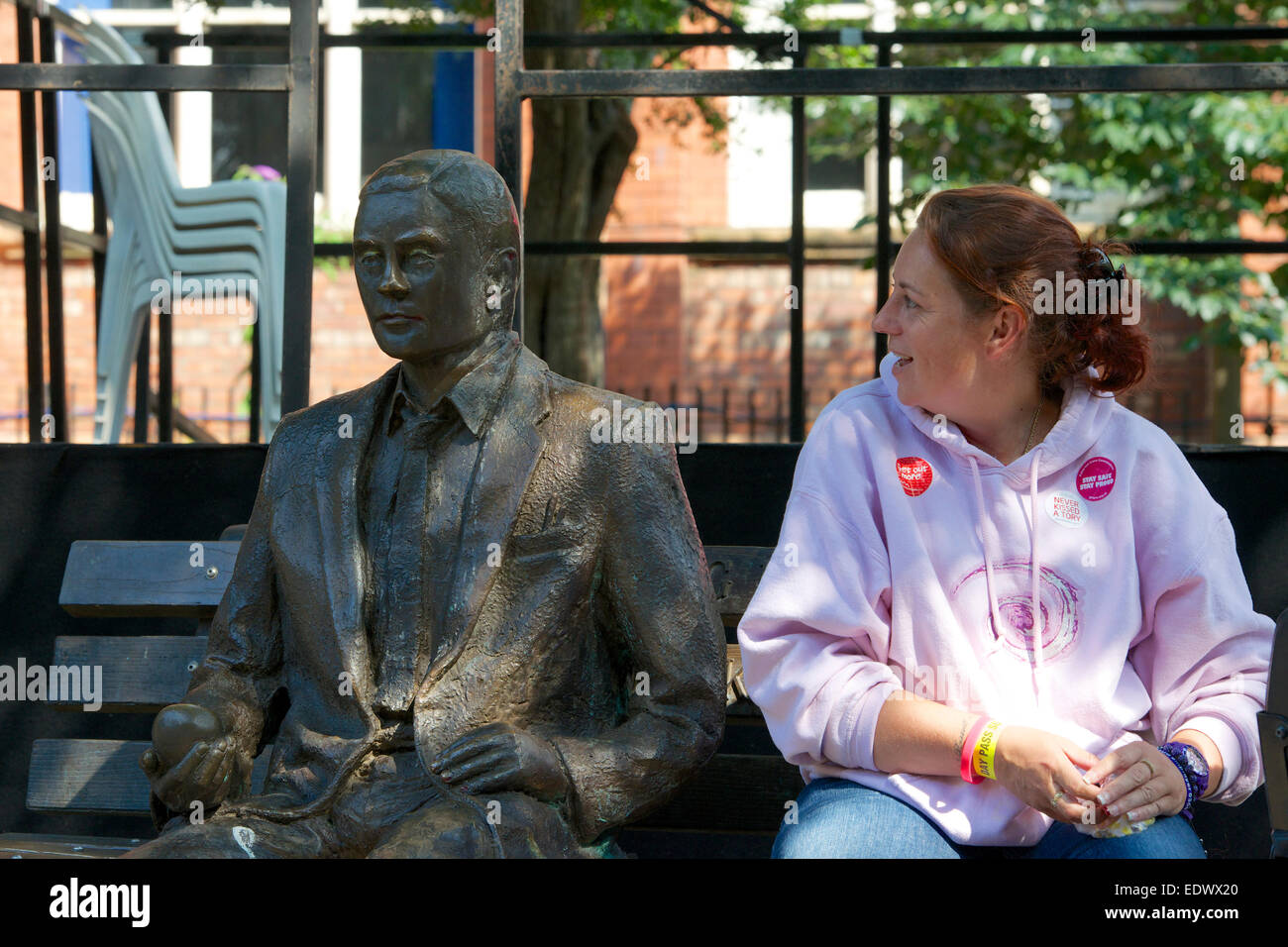 Woman sits down beside the statue of Alan Turing in Sackville Gardens, Manchester. - Stock Image