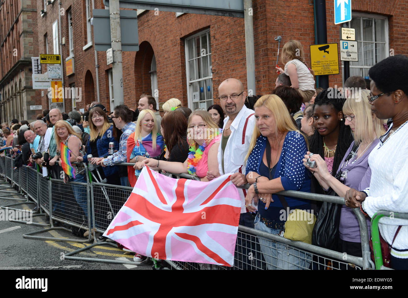 Onlookers hold a pink gay Union Flag at the Manchester Gay Pride Parade. - Stock Image