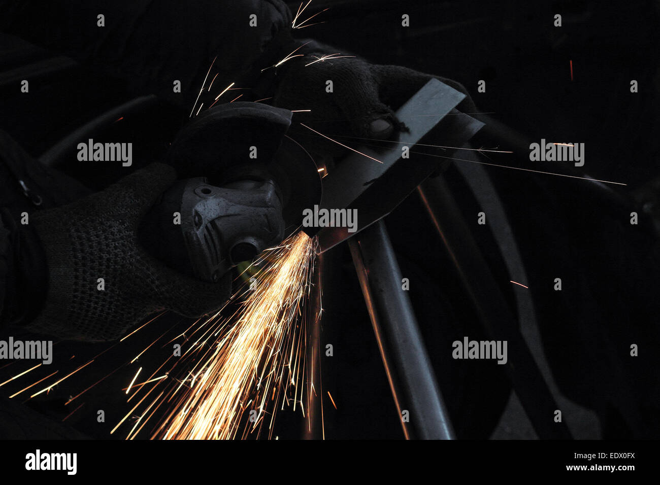 Sparks from the angle drive grinder against a dark background. - Stock Image
