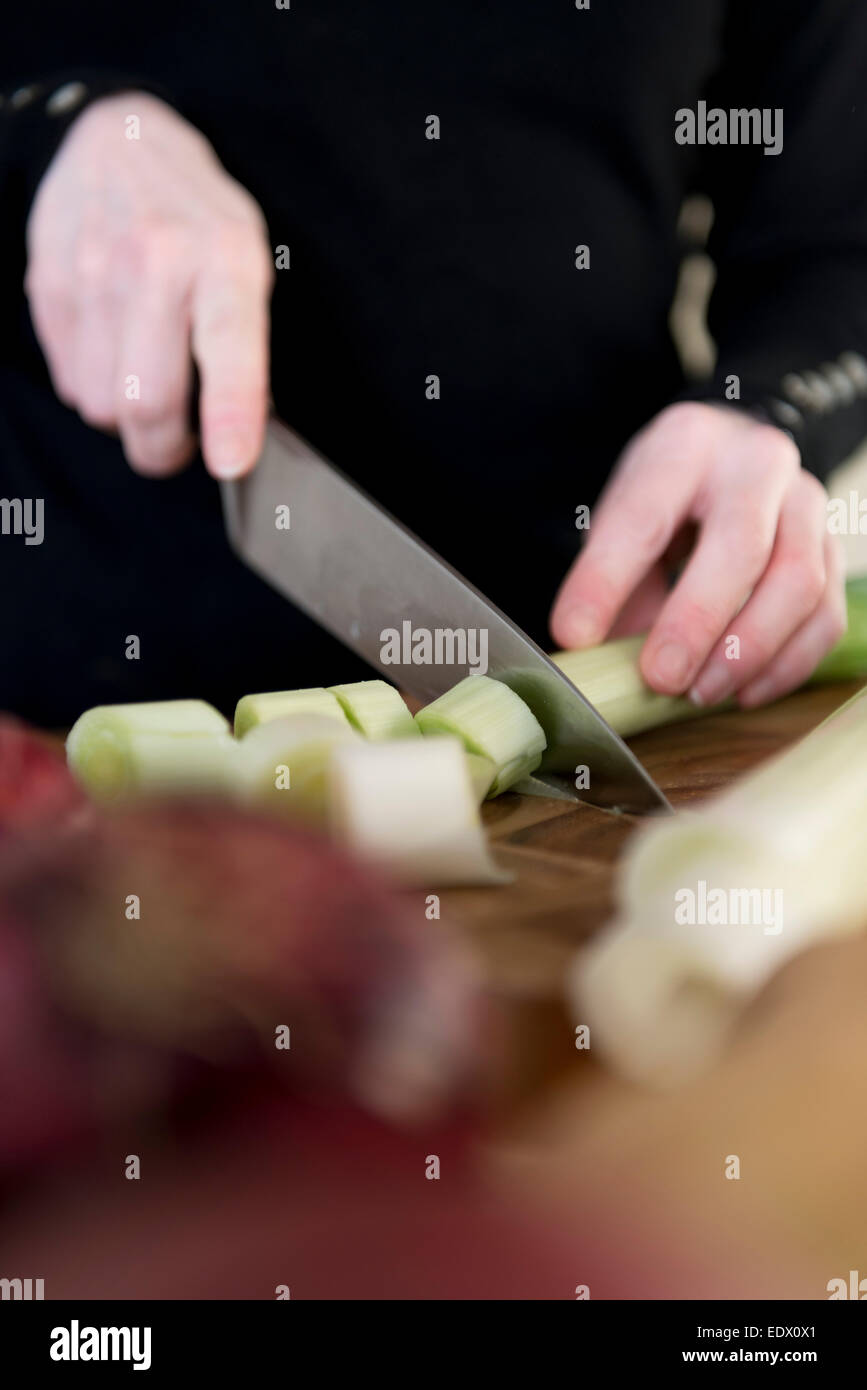 A womans hands slicing a leek. - Stock Image