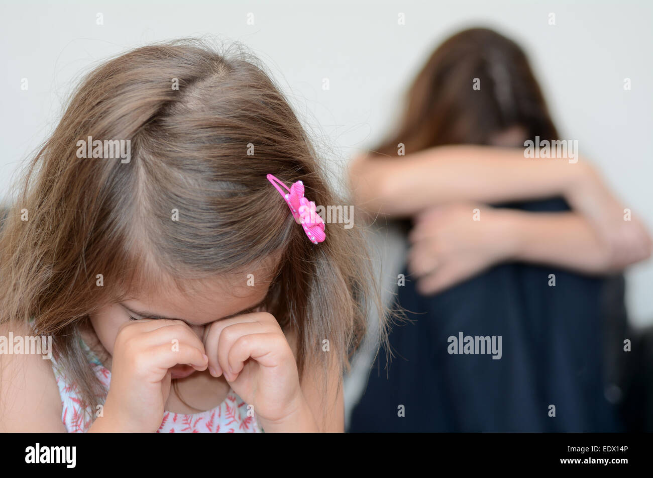 Little girl (age 05) cring with her desperate mother in background - Stock Image