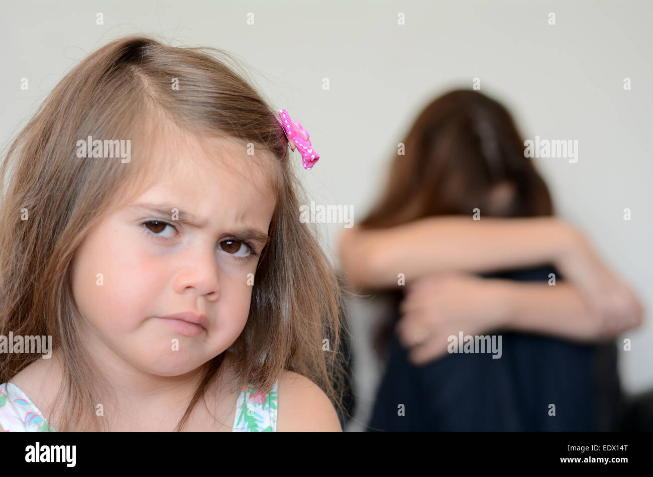 Little girl (age 05) having a temper tantrum with her desperate mother in background - Stock Image