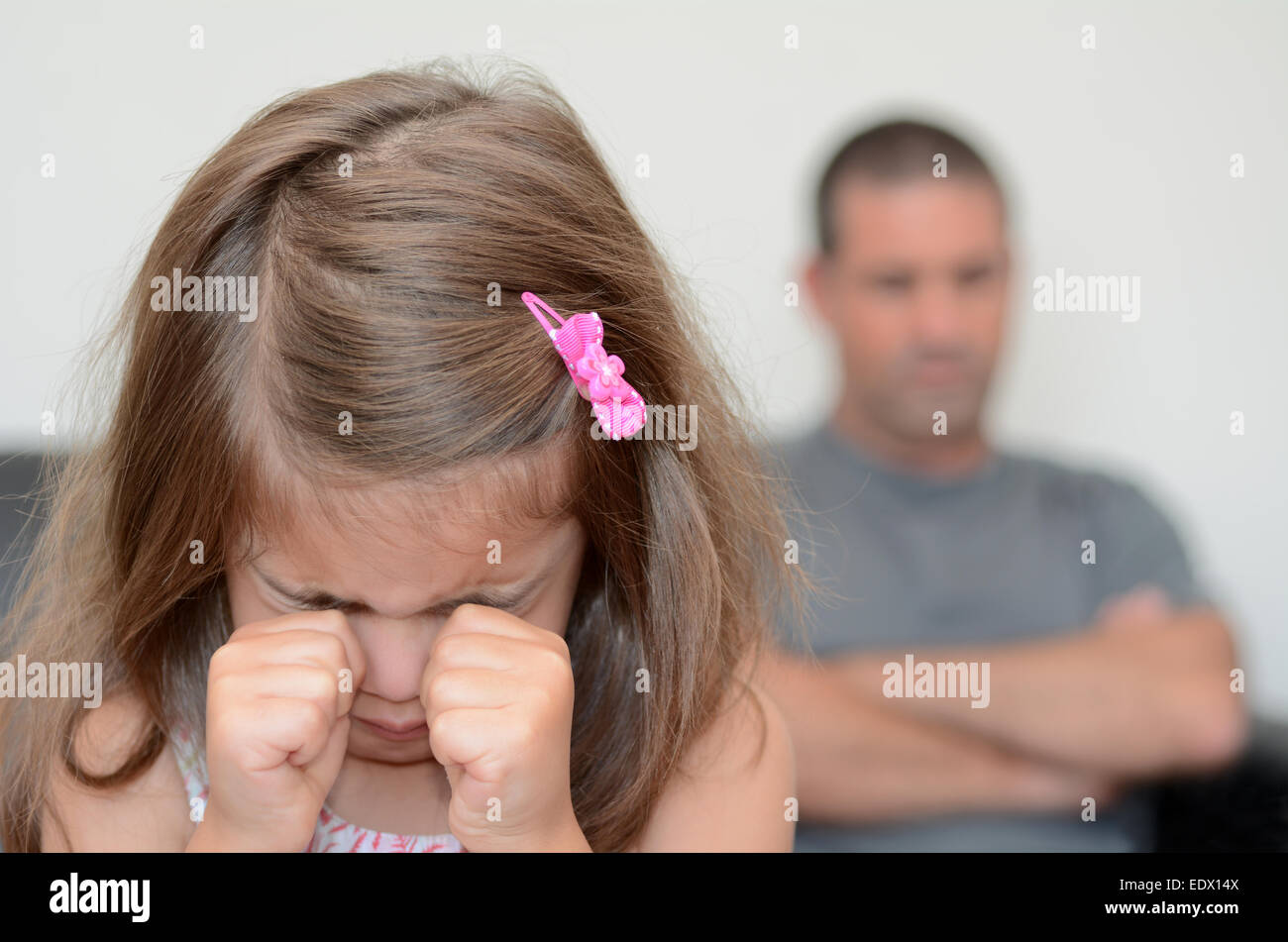Little girl (age 05) having a temper tantrum with her desperate father in background - Stock Image