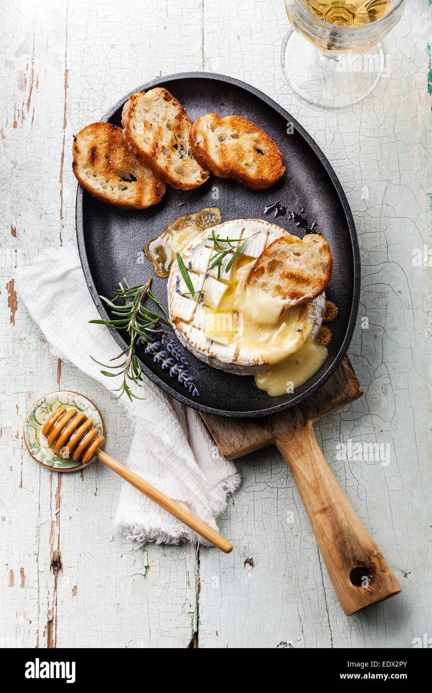 Baked Camembert cheese with toasted bread on cast-iron frying pan - Stock Image