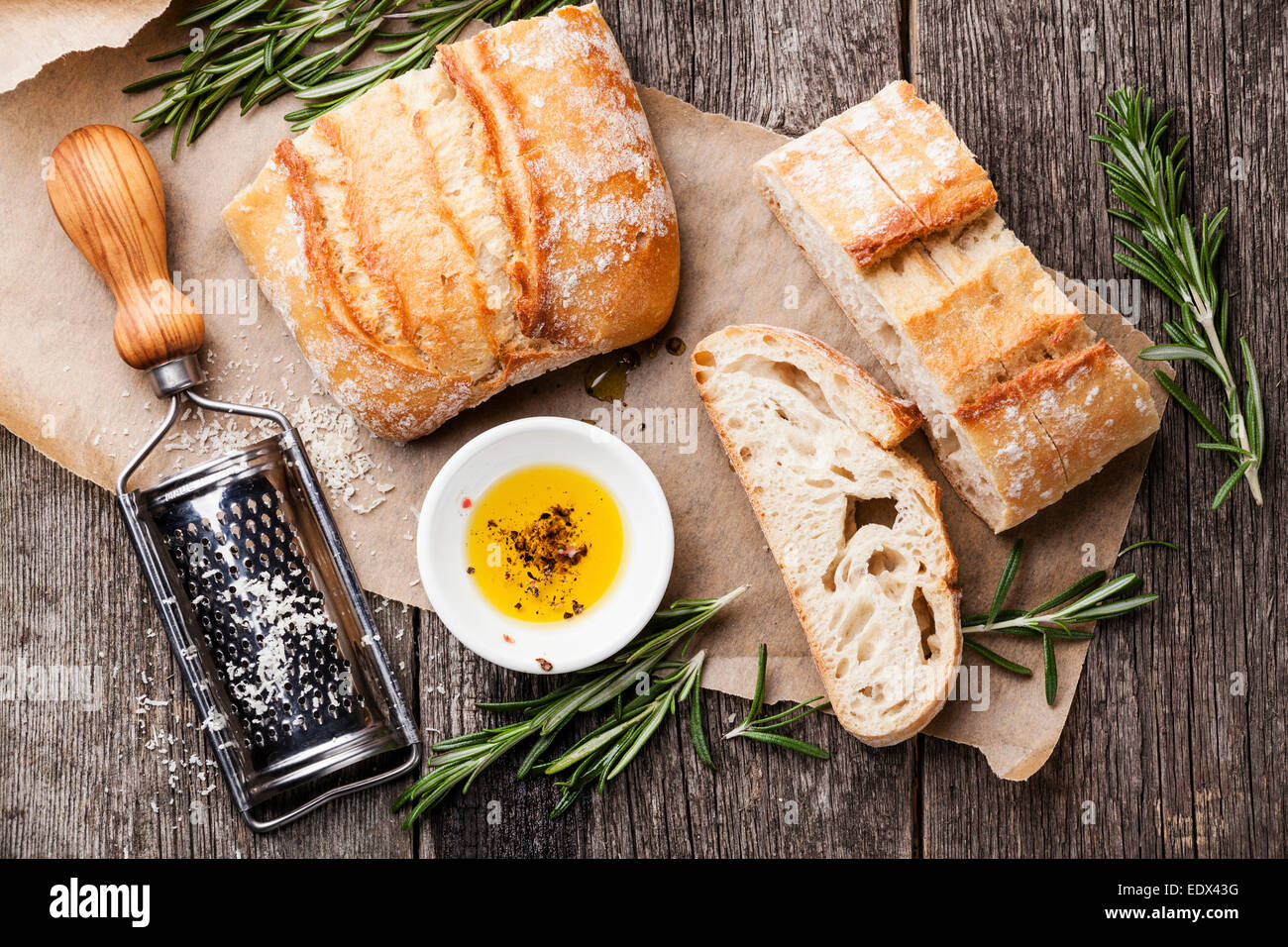 Sliced bread Ciabatta and extra virgin Olive oil on wooden background - Stock Image