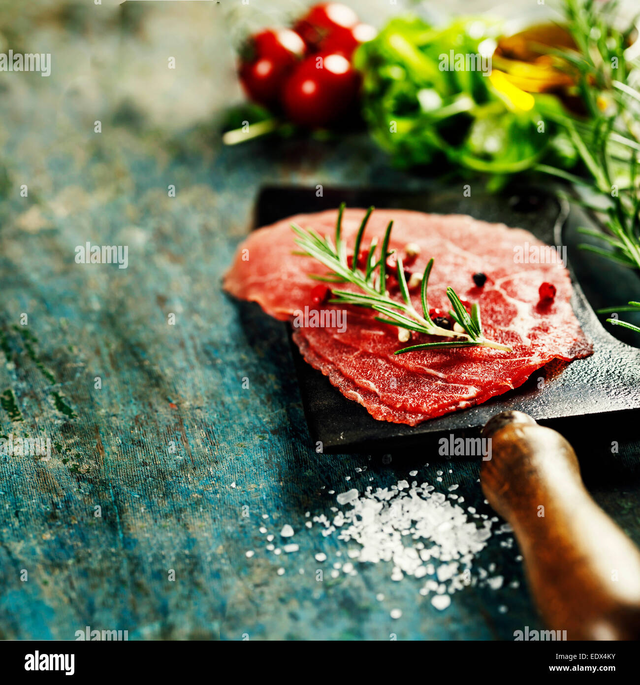 vintage cleaver and Beef Carpaccio on dark background - Stock Image