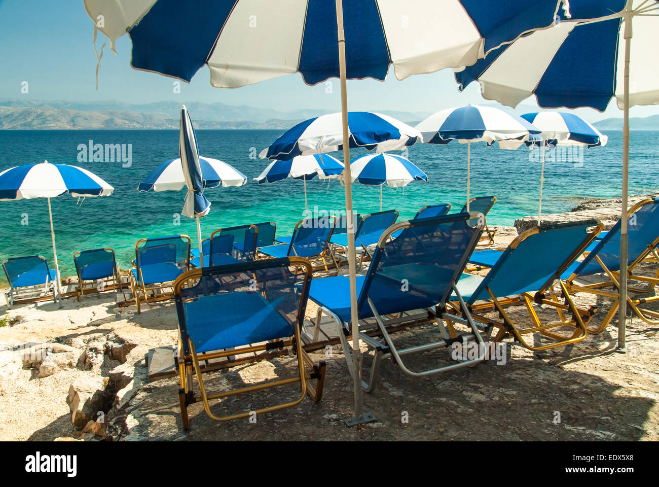 Sunbeds and umbrellas (parasols) on Kassiopi Beach, Corfu Island, Greece Stock Photo