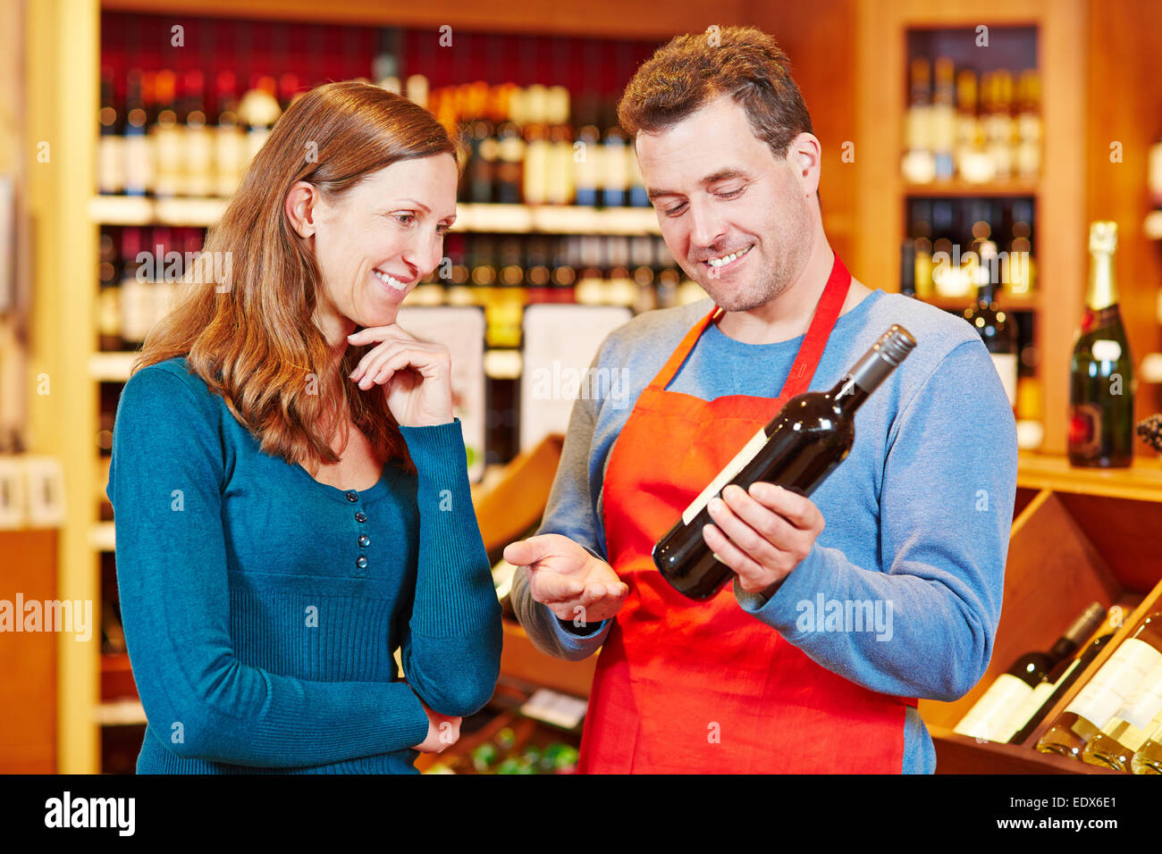 Sommelier in wine store giving woman recommendation for bottle of wine - Stock Image