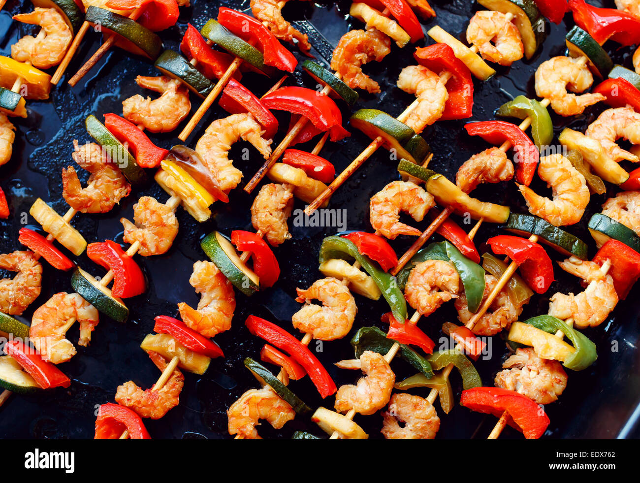 shrimp kebabs on black baking, diagonally - Stock Image