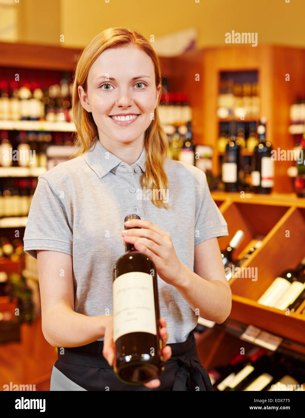 Smiling sommelier in wine shop recommending bottle of red wine - Stock Image