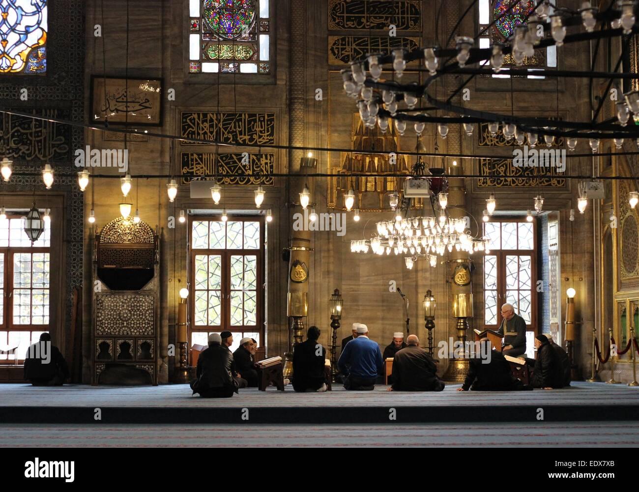 Men reading Qur'an and praying, Yeni Cami (New Mosque), Eminonu, Istanbul, Turkey. - Stock Image