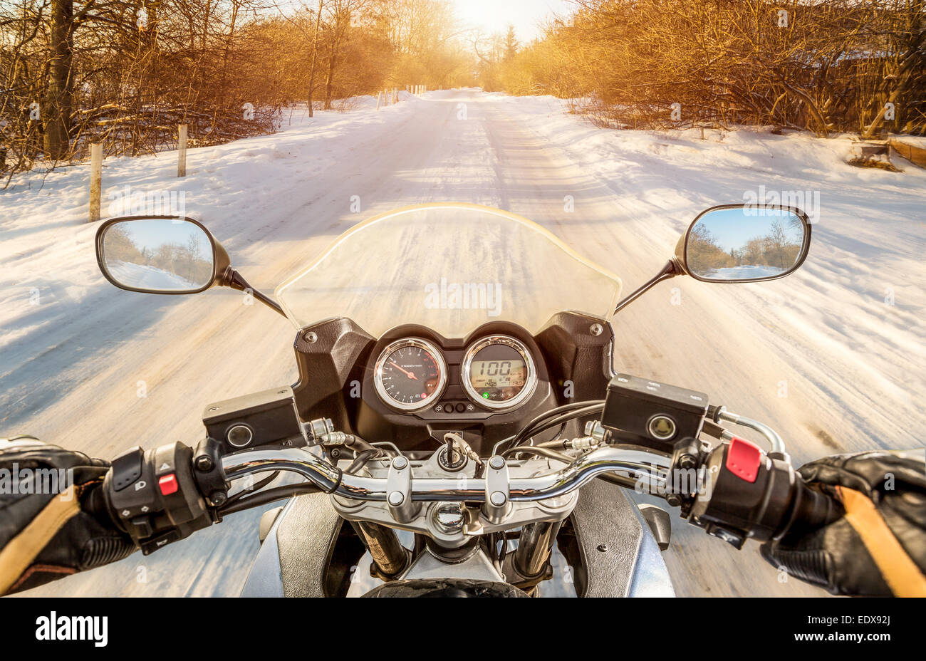 Biker rides on winter slippery road. First-person view. - Stock Image