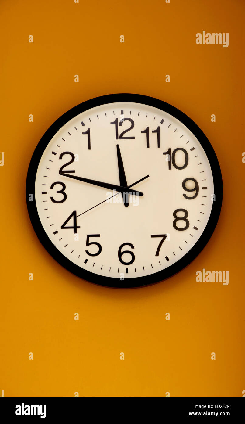 Wall clock with the order of the numbers inverted - Stock Image