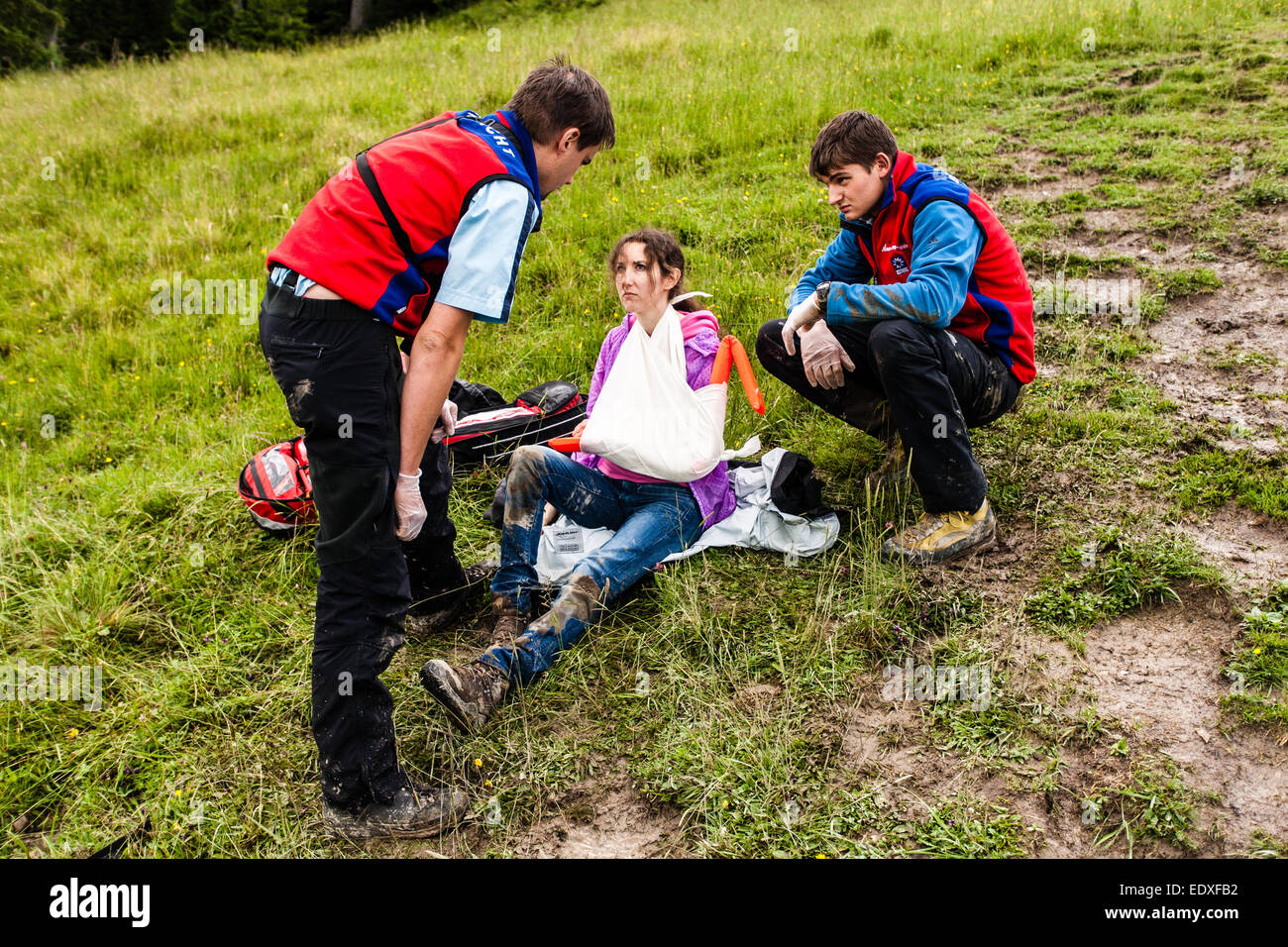 Woman being helped by mountain rescue team after breaking her arm after hiking in the Bavarian Alps, on waterlogged - Stock Image