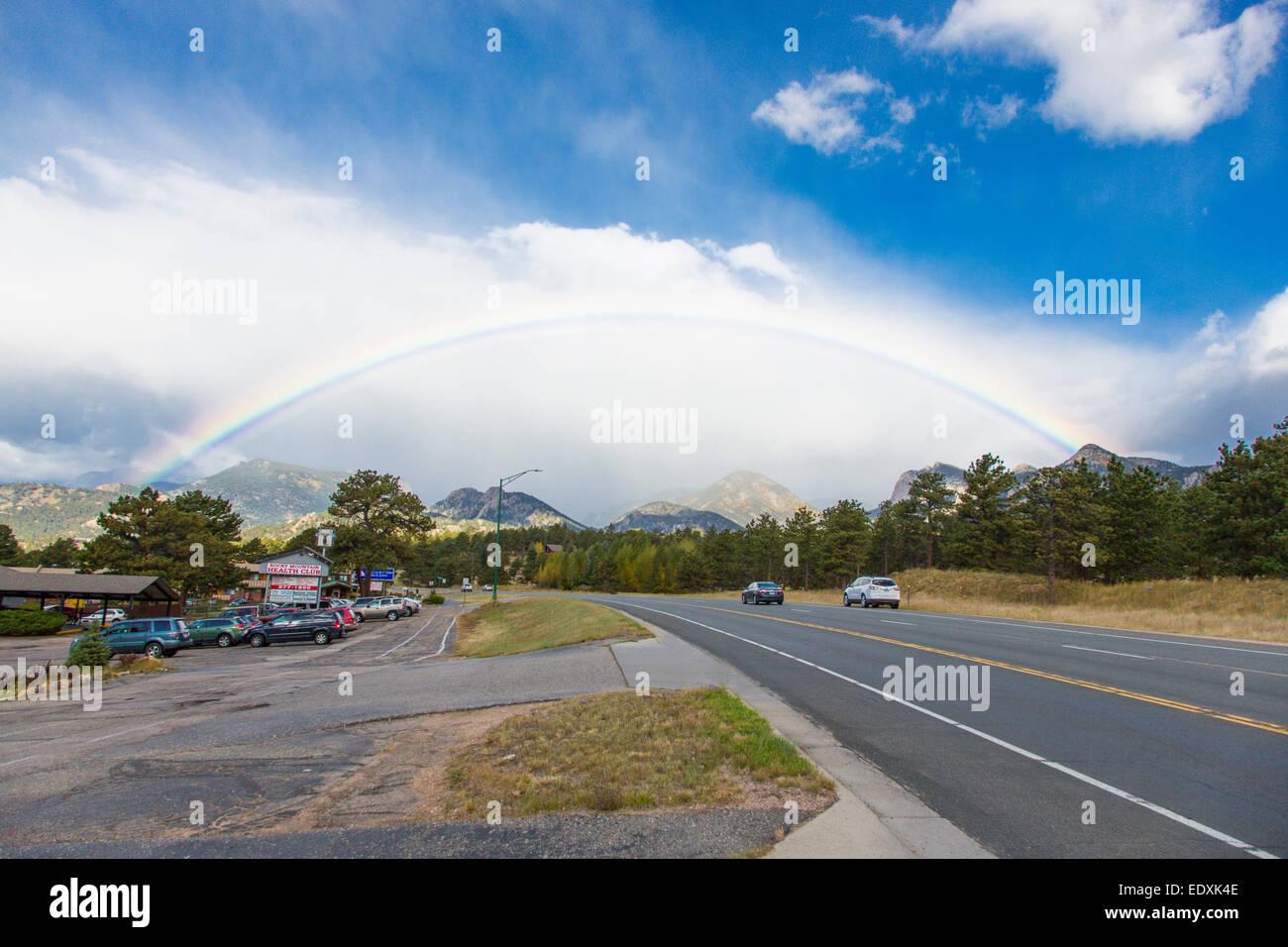 Full rainbow over Rocky Mountain National Park in Estes Park Colorado - Stock Image