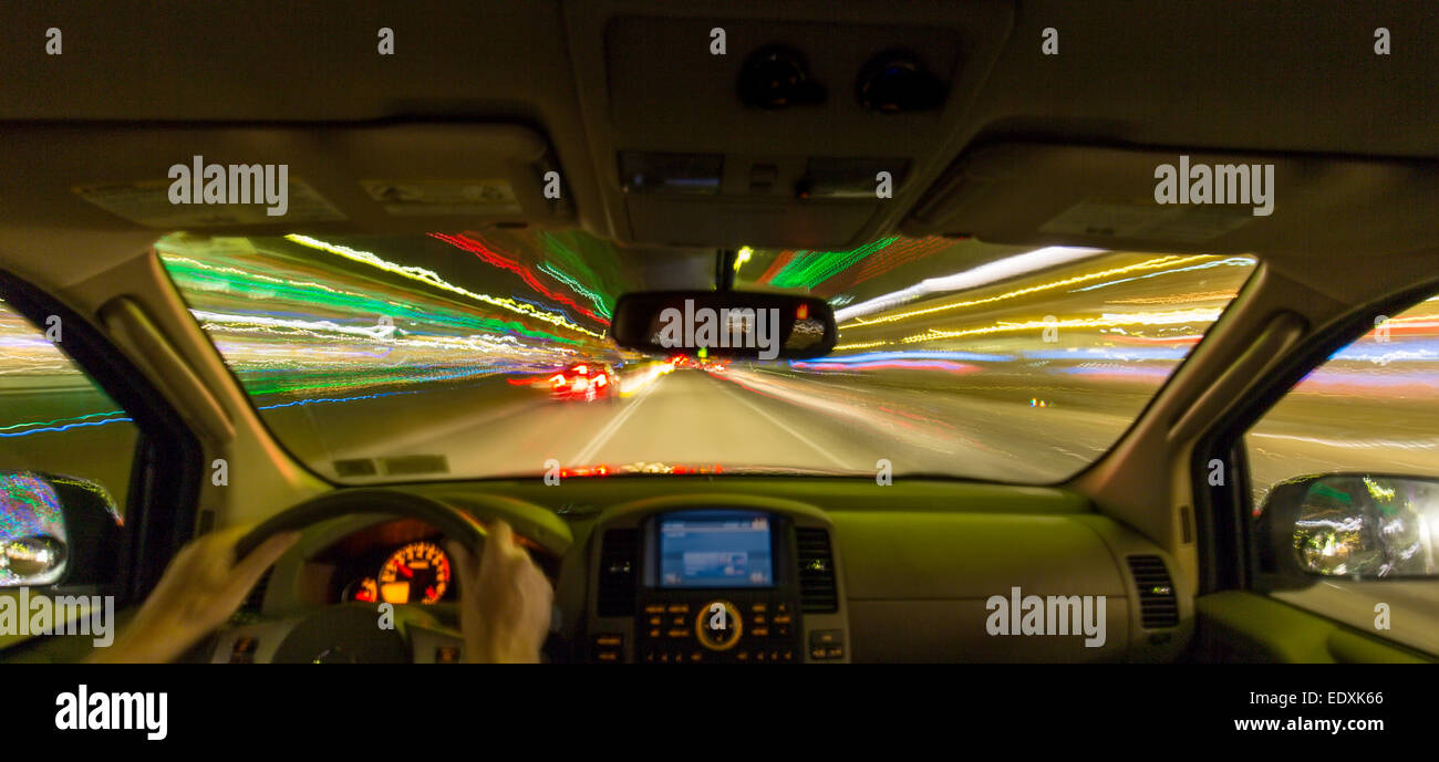 Night view out windshield of car while driving with blurred roadway and lights - Stock Image