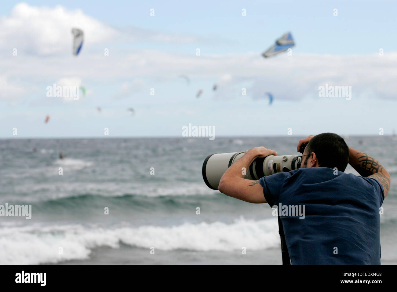 photographer wearing glasses uses a long Canon telephoto lens at a sports event - Stock Image