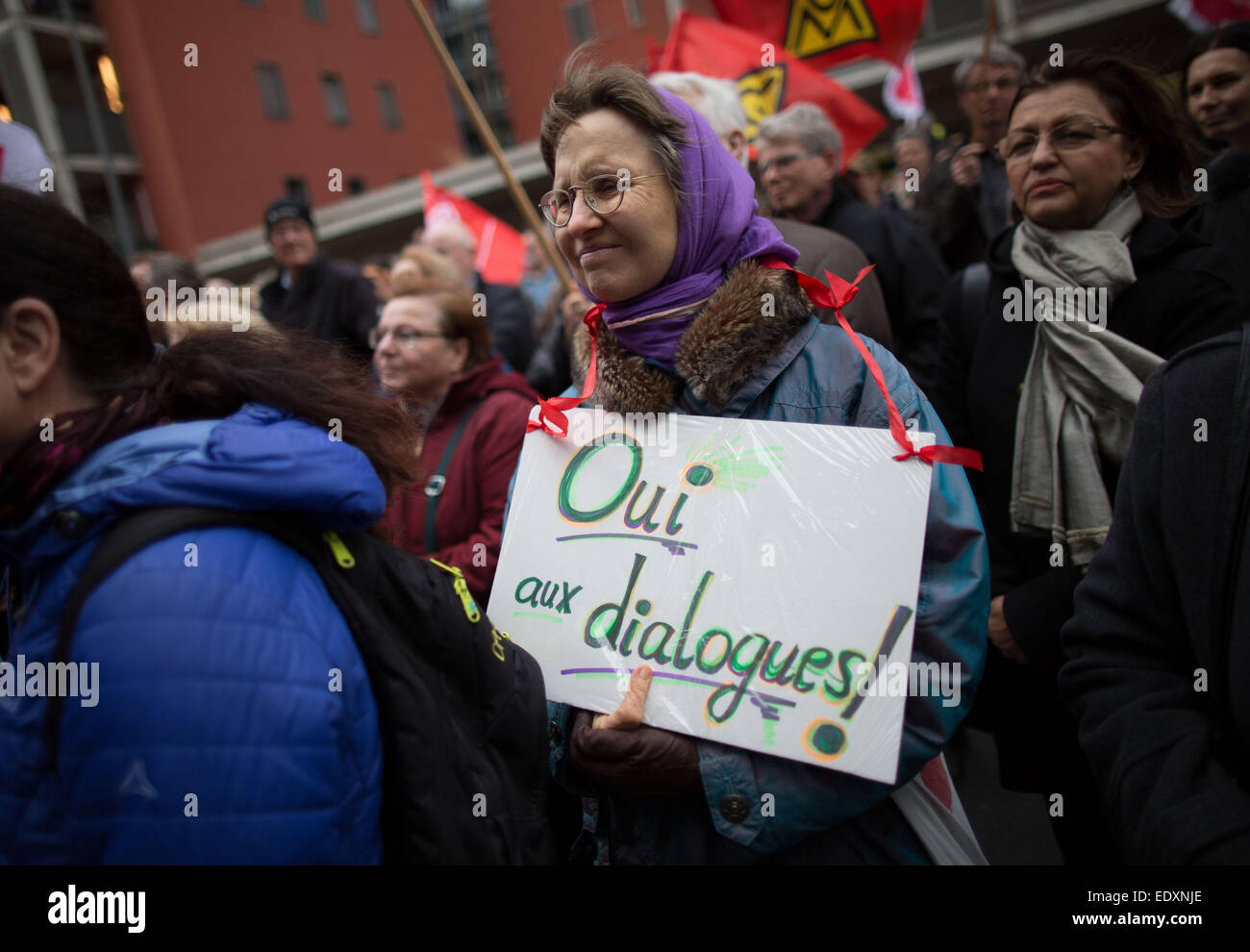 A woman carries a sign which reads 'Oui aux dialogues' (Yes to Dialogue) during a rally to commemorate the - Stock Image
