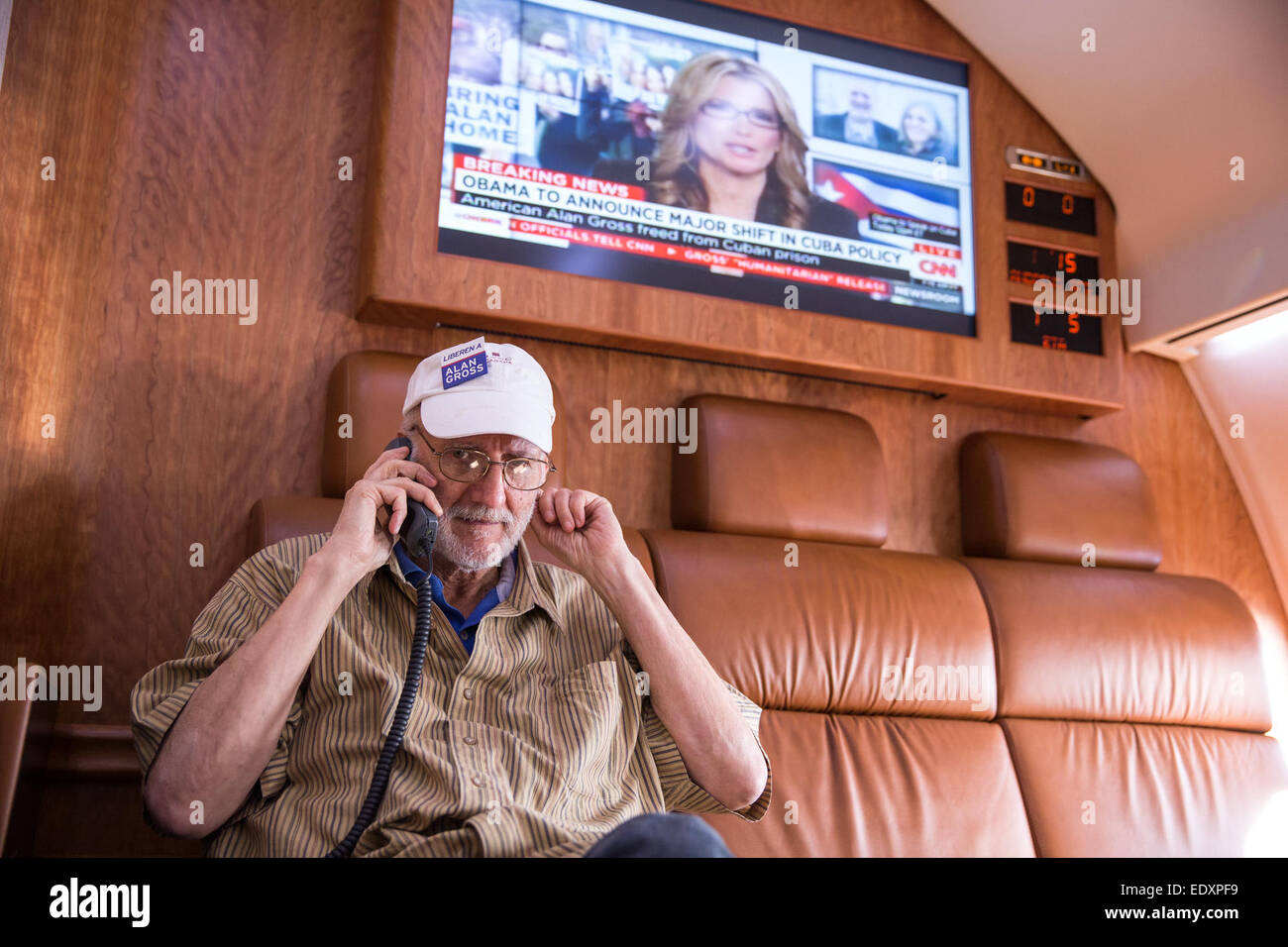 Alan Gross talks with President Obama onboard a government plane headed back to the US, Dec. 17, 2014. - Stock Image