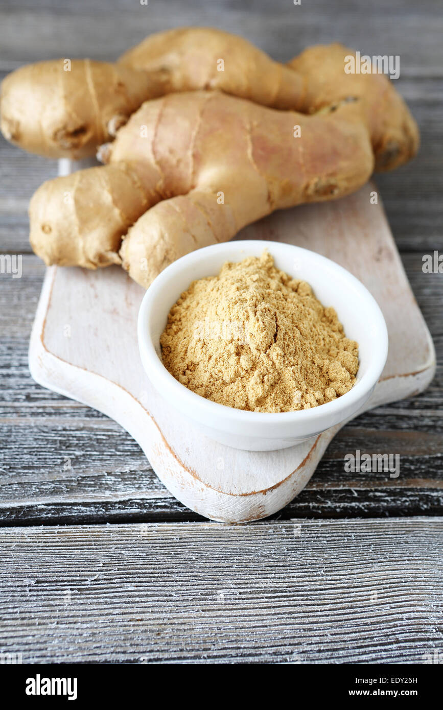 Ginger powder in a bowl and root - Stock Image