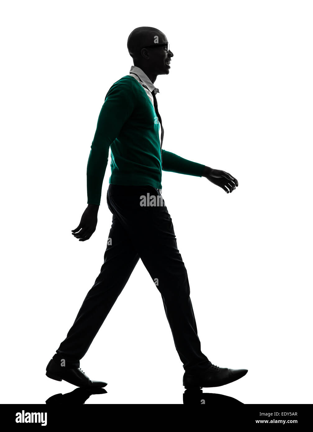 one african black man walking in silhouette studio on white background - Stock Image