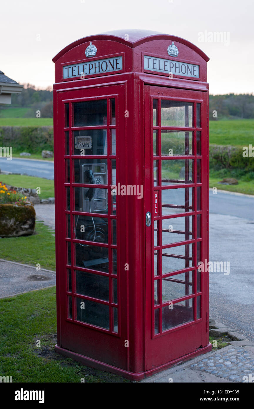 Close-up of traditional bright red telephone box or kiosk standing by country lane, an amenity in Bolton Abbey village, - Stock Image