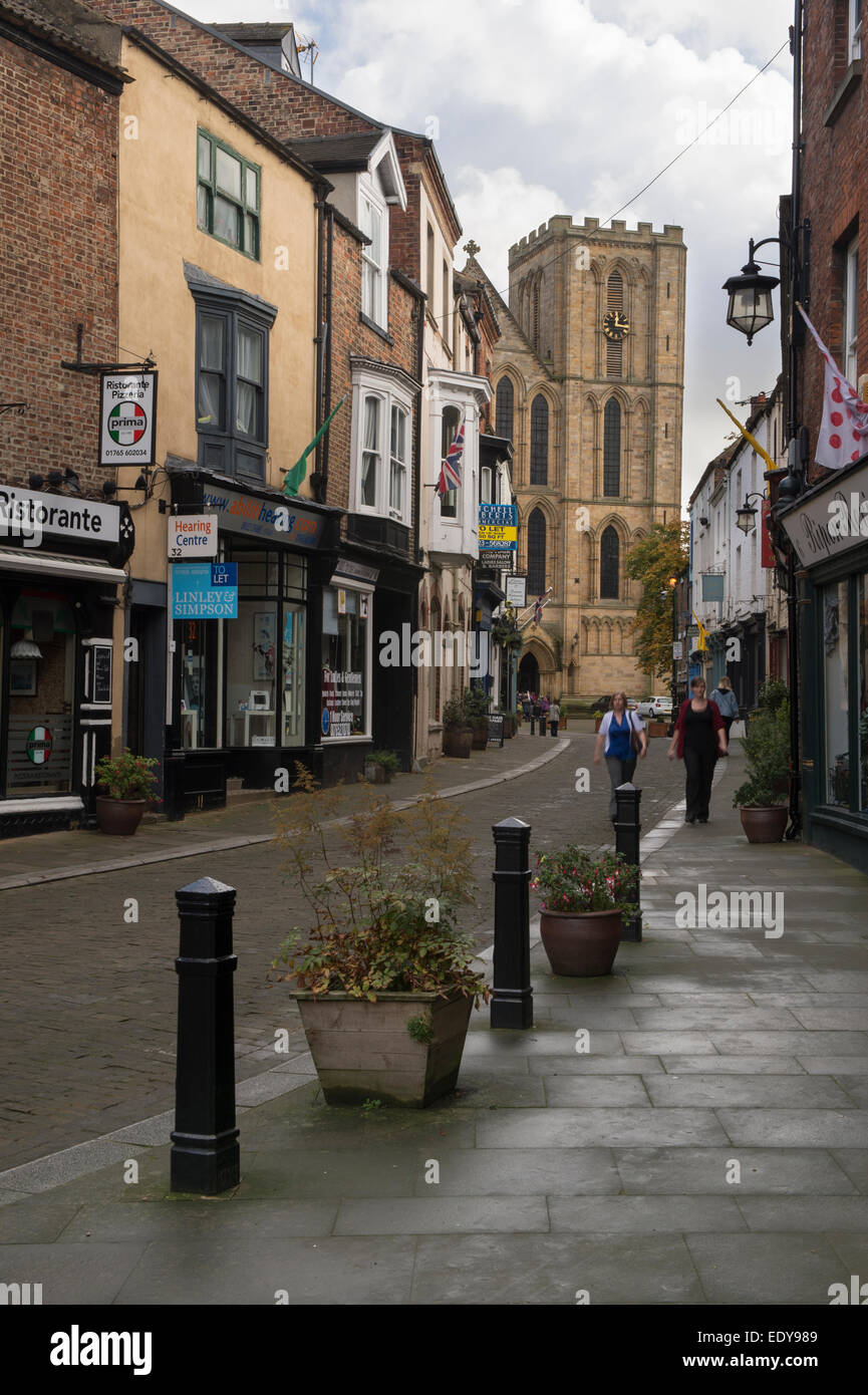 Looking down narrow, historic Kirkgate, lined with small shops, towards a tower on the west front of Ripon Cathedral - Stock Image