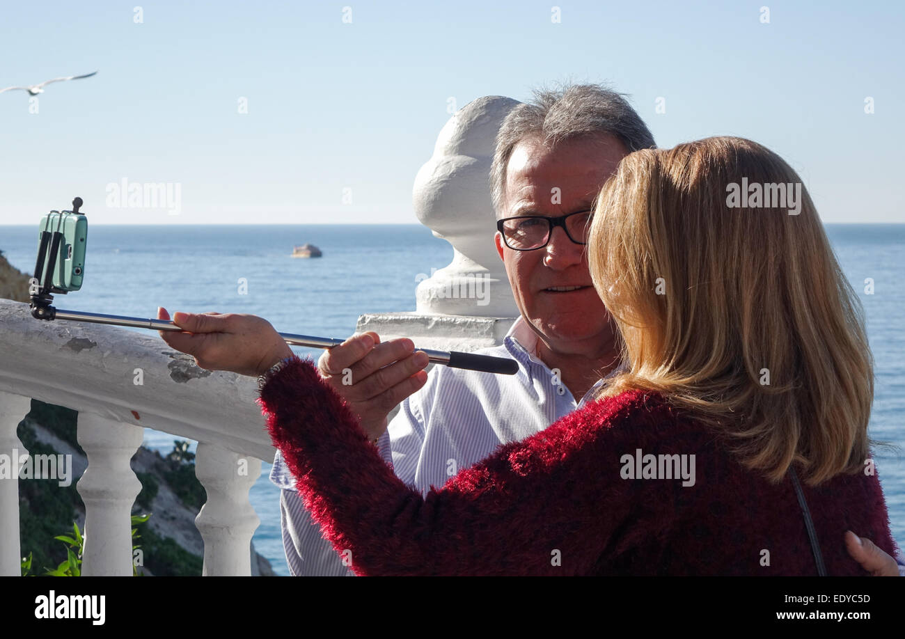 Mature couple taking selfy using selfie stick and cell phone, mobile phone picture on sunny day at the sea side - Stock Image