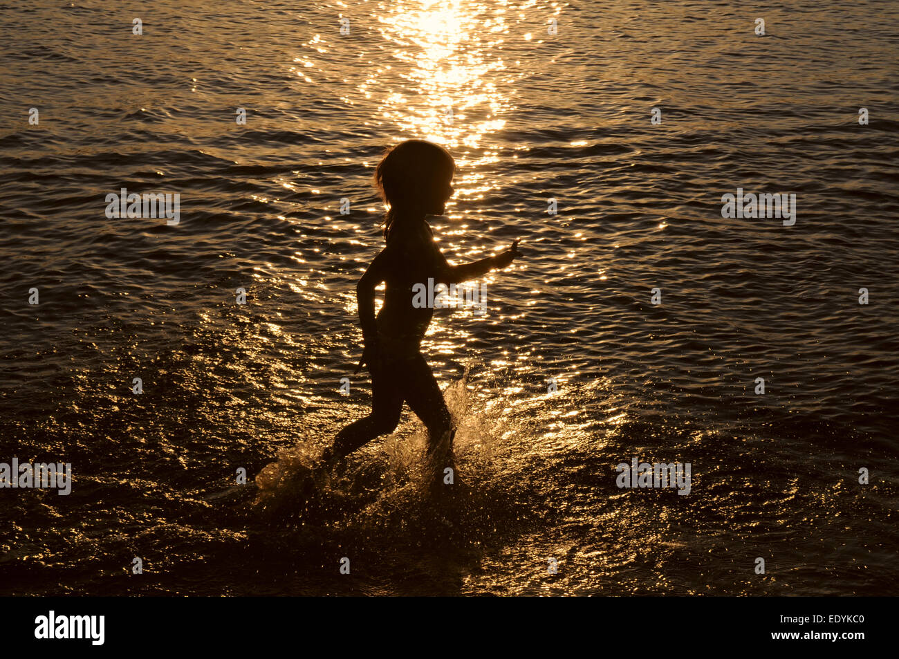 Little girl is running on the shallow.Only girl's silhouette against the background of sunset is seen. - Stock Image