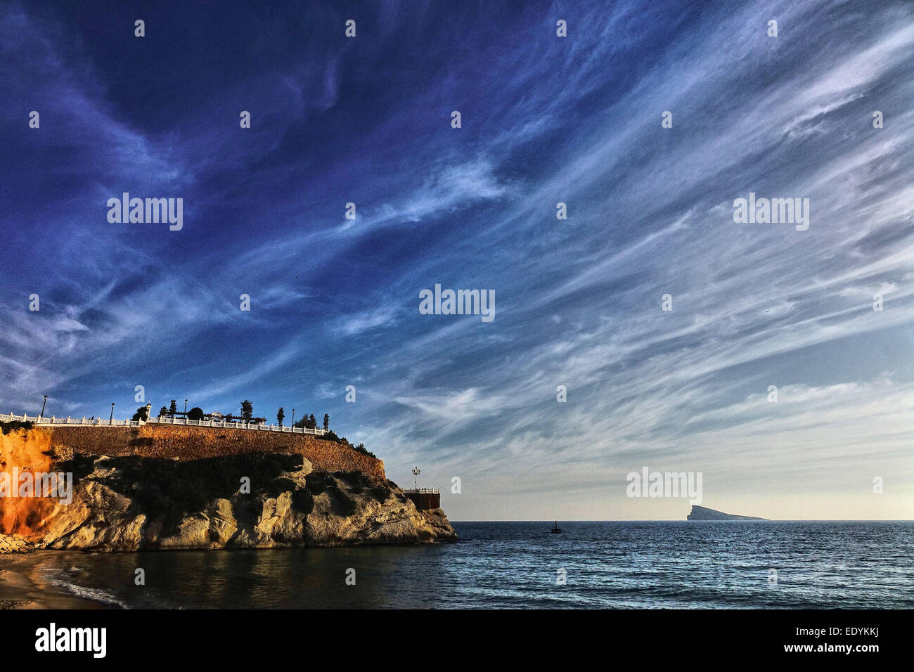 Benidorm promontory from beach with vivid blue sky, wispy  clouds, sea and Peacock Island, Spain - Stock Image