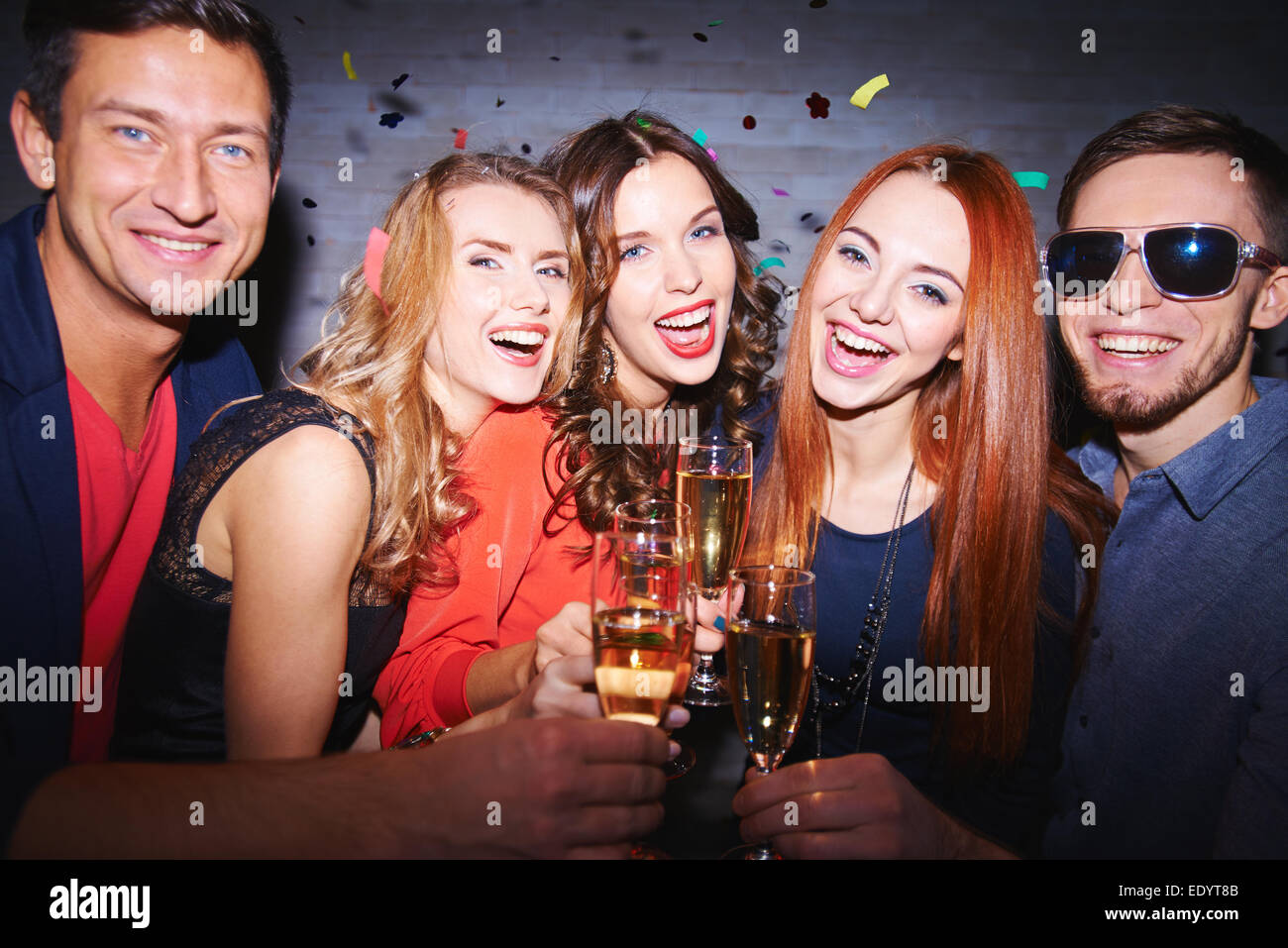 Ecstatic friends with champagne having party - Stock Image
