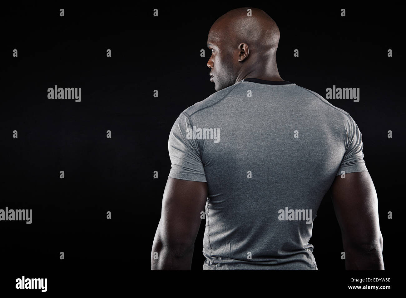Rear view of fit young man with muscular build standing against black background. Afro American fitness model in - Stock Image