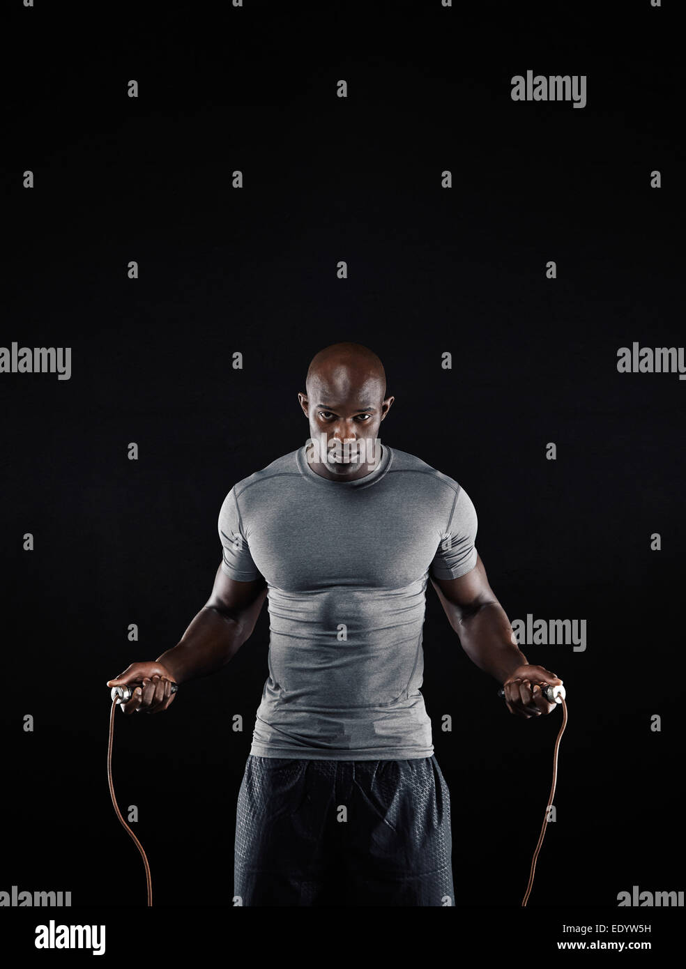 Studio shot of masculine African man skipping rope with copy space. Portrait of muscular young man exercising with - Stock Image