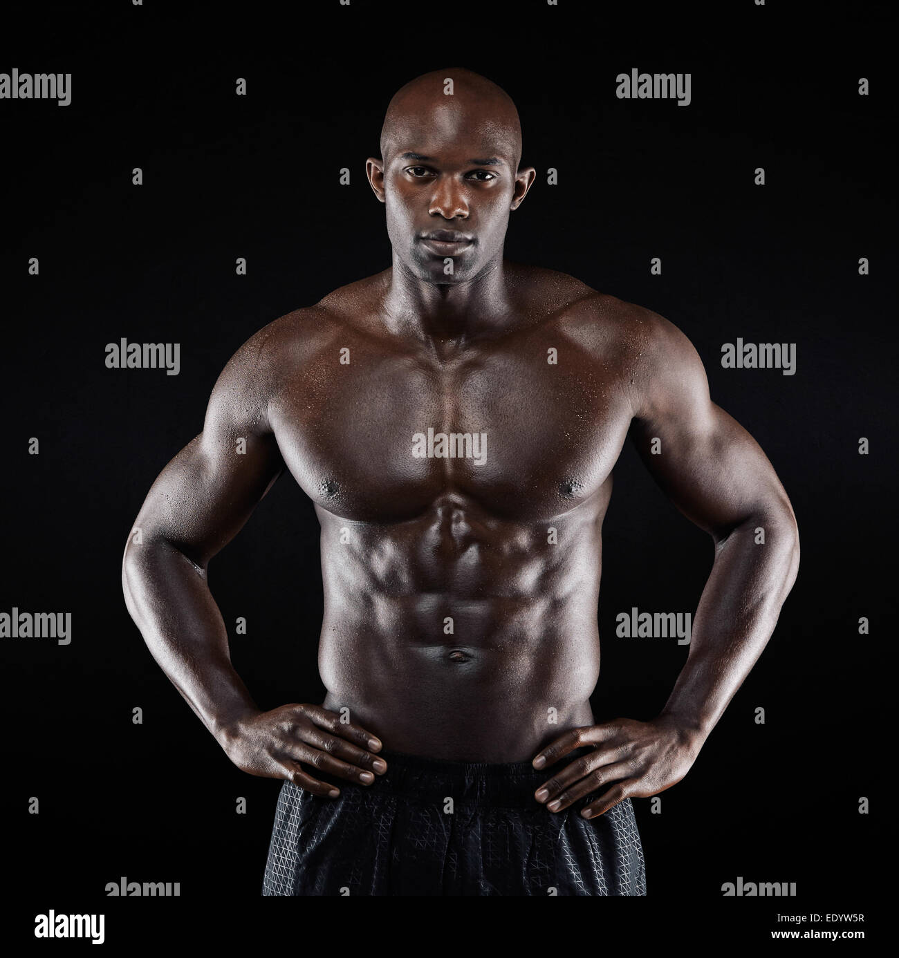 Portrait of a strong afro-american man showing off his physique against black background. Shirtless male model posing. - Stock Image