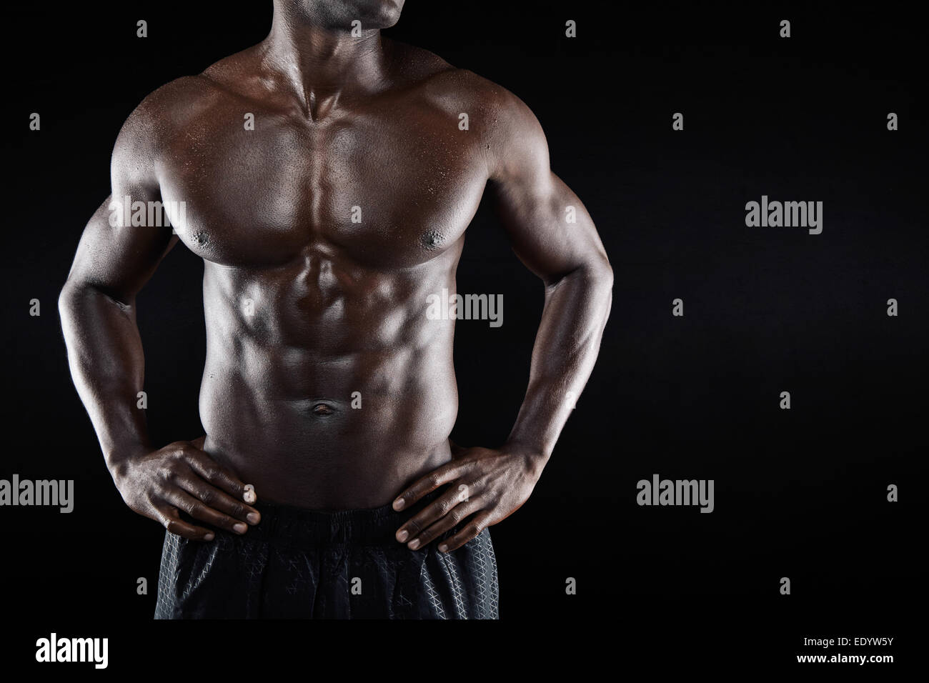 Cropped image of shirtless African man with hands on hip while standing against black background. Close-up of torso - Stock Image
