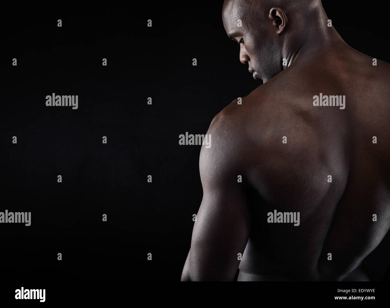 Rear view of young man with muscular build standing on black background. African shirtless male model with copy - Stock Image