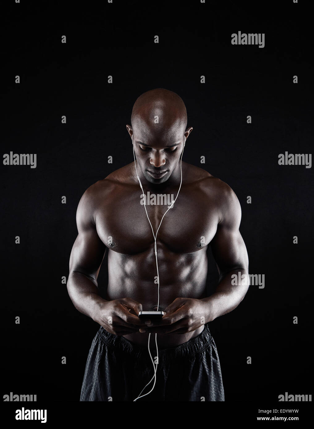 Portrait of young man listening music on mobile phone against black background. Shirtless African muscular male - Stock Image