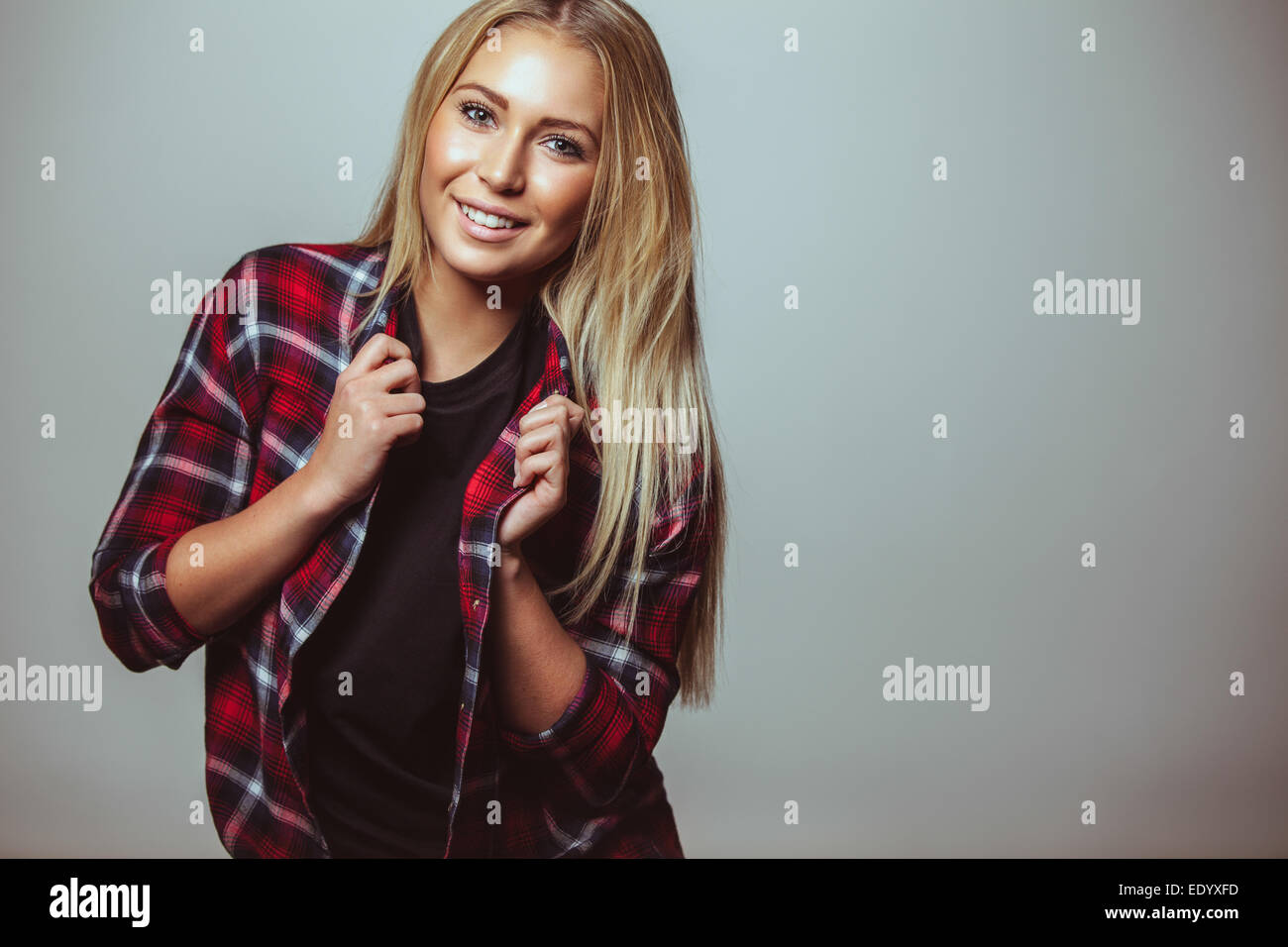 Portrait of happy young woman in casual wear against white wall. Young teenager looking at camera with a sweet smile. - Stock Image