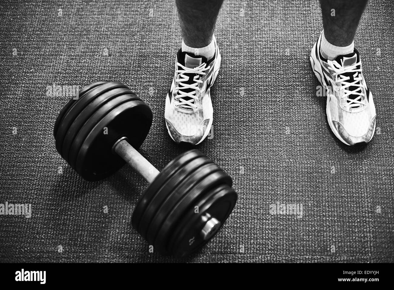 Feet of young man in sneakers and barbell near by - Stock Image