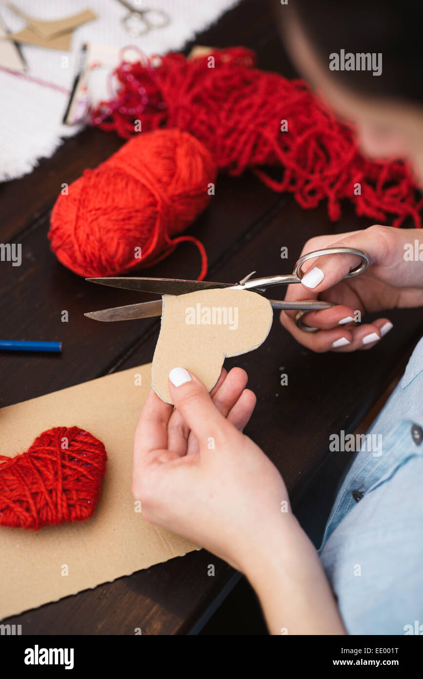 Woman creating red woolen heart - Stock Image