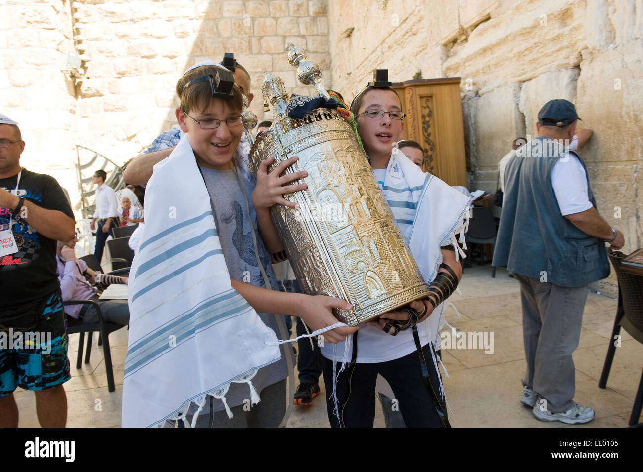 Two 13 years old boys are carrying a torah scroll during a Bar Mitzvah ritual at the Wailing wall - Stock Image