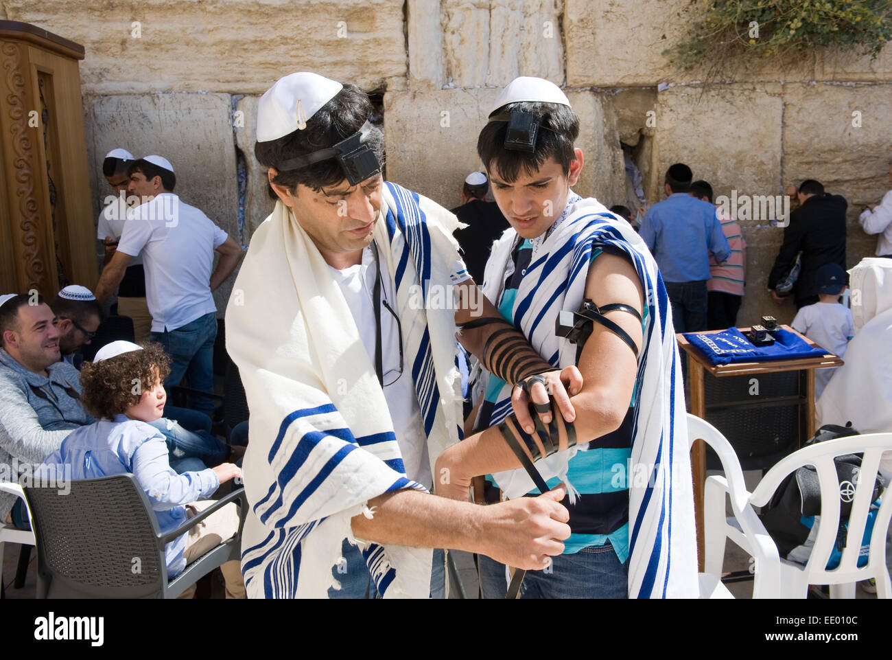 A jewish man is preparing the tefillin around the arm of a boy of 13 years old before his Bar mitzvah - Stock Image