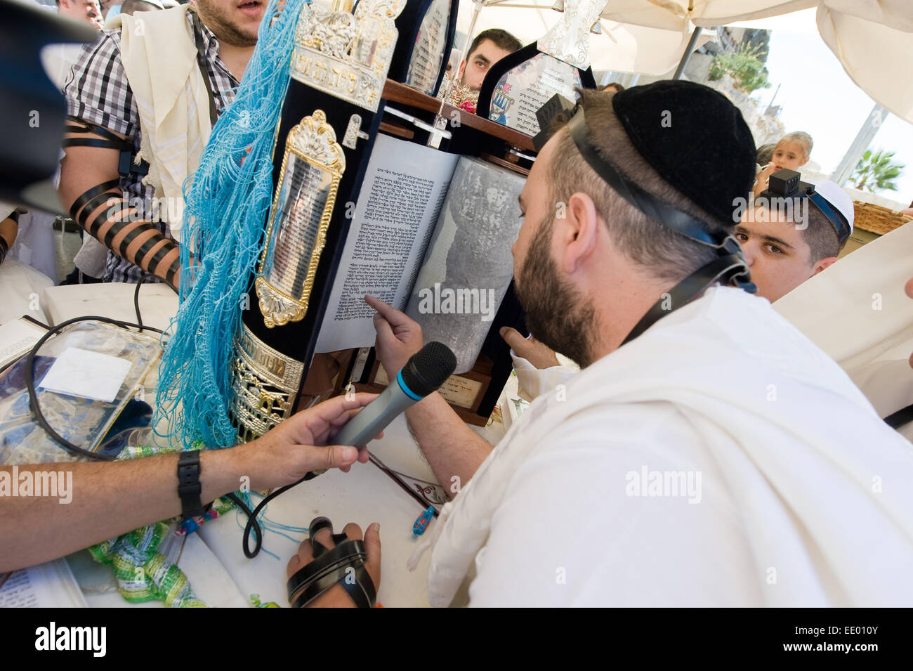 A jewish man is reading from the torah during a Bar Mitzvah ritual at the Wailing wall in Jerusalem - Stock Image
