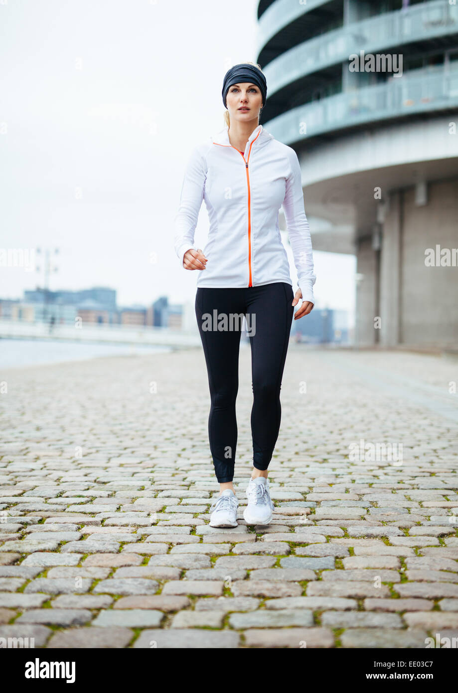 9aa98aef Full length portrait of a pretty young woman in sportswear exercising  outdoors. Woman power walking